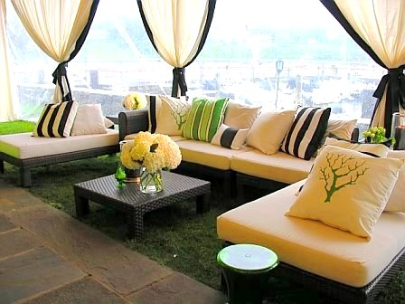 Black rattan outdoor furniture and custom pillows at a wedding designed by Delaney Todd Bagwell