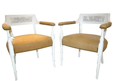 Two carved chairs with faux bamboo legs painted white, cane backs and upholstered in caramel leather with nail head trim from Pieces