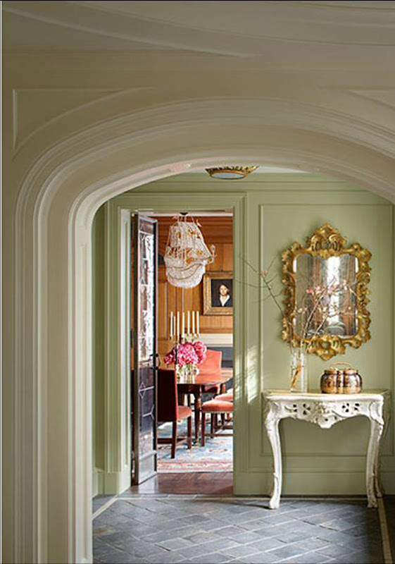 Room with pale green walls, a white console table with curved legs, an ornate gold mirror and stone tile floors outside a New York City apartment's dining room designed by Katie Leede