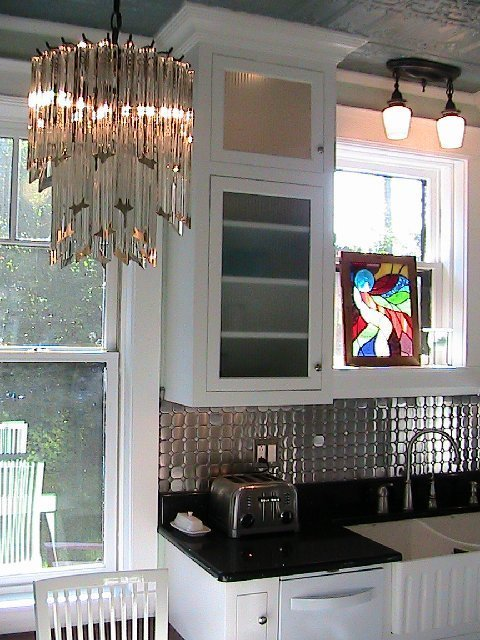 Kitchen after remodeling with a crystal chandelier, Diamond Tech-Metal Series Mosaic Octagon Dots tile backsplash, black counters, white cabinets and a stained glass accent piece
