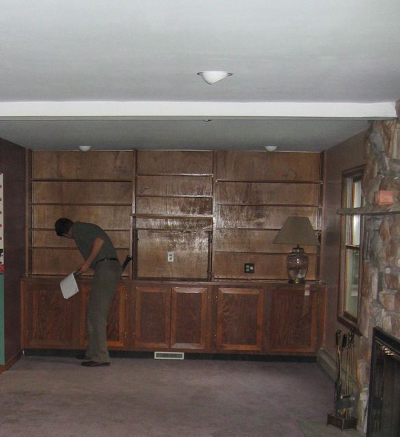 Living room with outdated wood paneling and beaten up carpeted floors