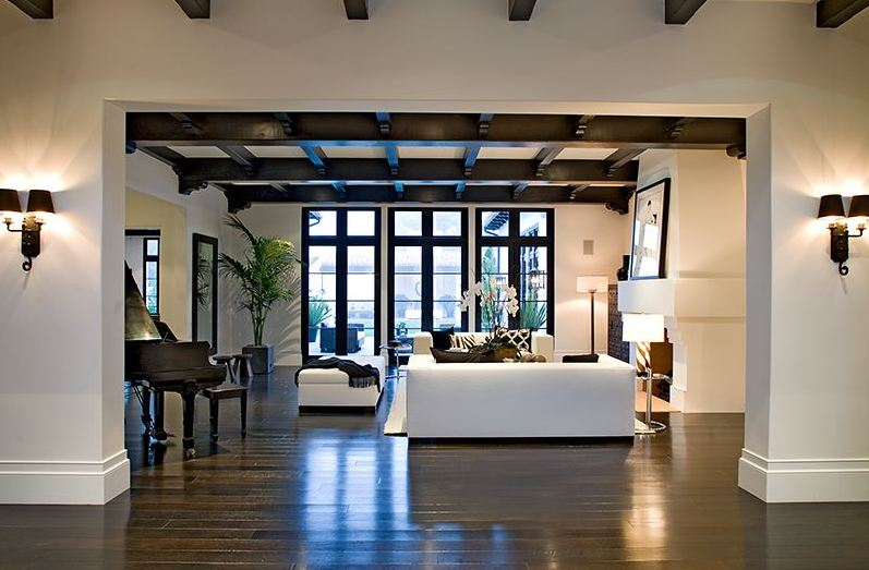 Foyer in a Spanish revival home with painted black exposed beams and a view of the living room