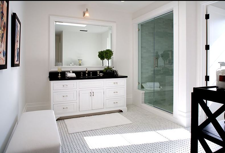 Black and white Master bathroom in a Spanish revival home with glass shower and a white bench