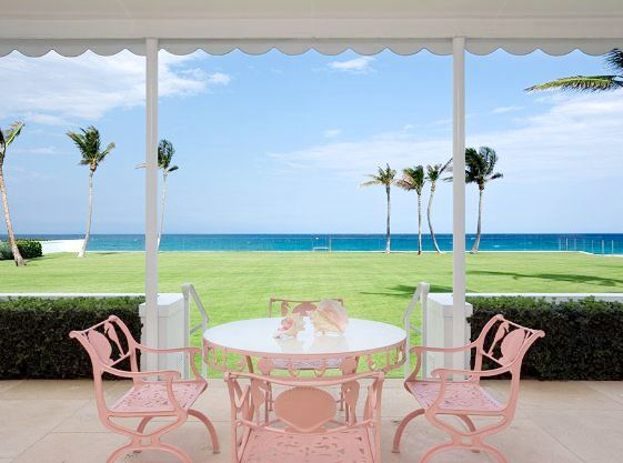 Pink outdoor table and chairs with a large green lawn and an ocean view