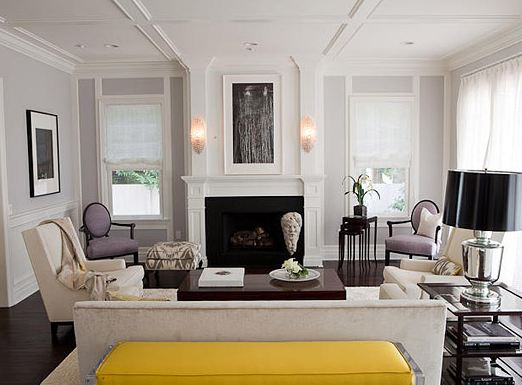 Living room in the Pacific Palisades with coffered ceiling,  light grey walls, a white fireplace, dueling armchairs, a long grey sofa, dark wood floor and a bright yellow bench