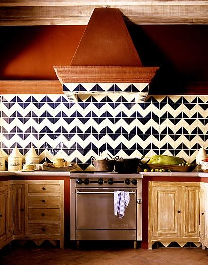 Kitchen with reclaimed wood cabinets and drawers, stainless appliances and a blue and white chevron tile backsplash