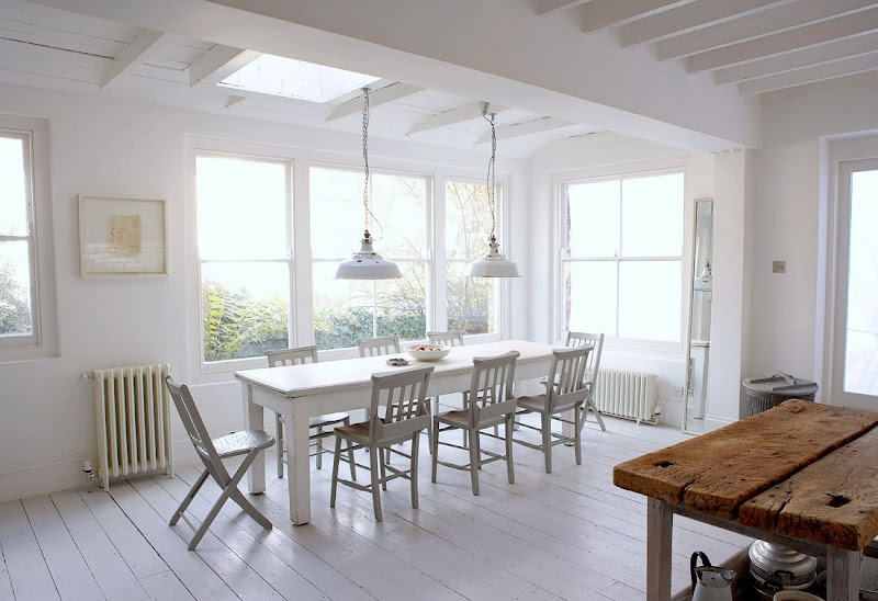 White rustic eat in kitchen with white washed floors, tables and chairs, exposed bulb lighting, and reclaimed butcher block island. 