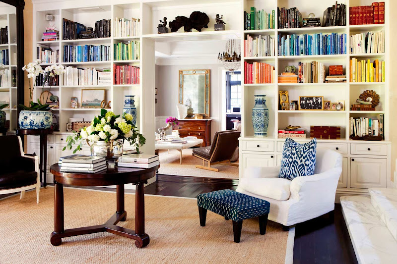 Living room with built in bookshelves full of books arranged by color, dark wood floor, white armchair with an ikat accent pillow and an upholstered blue ottoman with black legs, a sisal rug and a round wood table holding more books and a flower arrangement