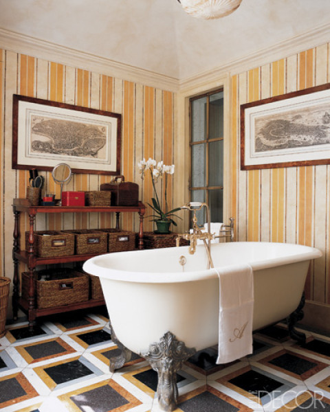 Bathroom with a claw foot tub, yellow and white striped wallpaper, decorative moudling, and a black, gold and silver tile floor