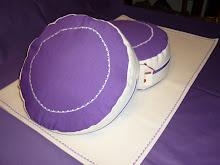 Cojines lila y blanco y  cubre esterilla.
