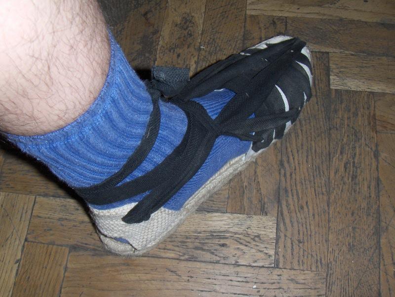 las pasas alrededor del tobillo y las atas, de forma que las tiras laterales queden lo bastante tensas para que la alpargata quede bien ajustada.
