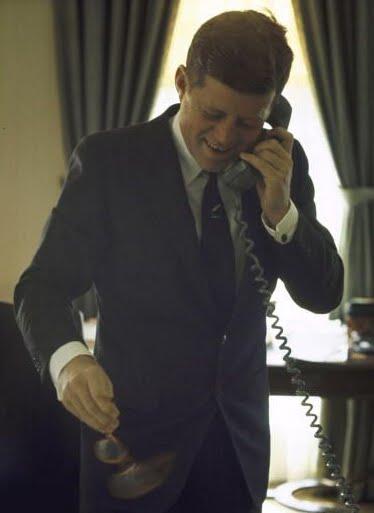 jfk in oval office. modren jfk the new president of the united states talks on telephone while  twirling his eyeglasses in oval office january 1961 in jfk