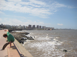 Johnny leaping over the sea wall along the seafront of Montevideo.