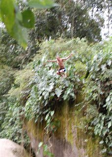 Noah jumping off rock into pool below in Paraty.