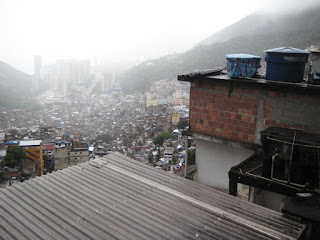 The whole of Rocinha Favela lays below us through the rain.  The hish rise buildings outside the favela can be seen at the bottom but the ocean is hidden in the mist.