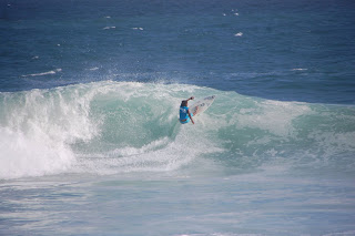 A professional surfer ripping up a wave at Ipanema Beach.