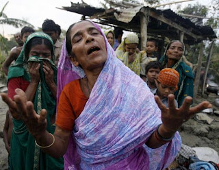 Cyclone Kills Hundreds in Bangladesh: Hasu Begum (R) and her sister Niru react after their 80-year-old mother was killed, when their house collapsed during the cyclone, in Bakerganj, 340 km (211 miles) southwest of Dhaka, November 17, 2007.  (Rafiqur Rahman/Reuters)
