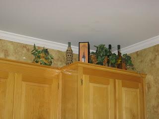 kitchen cabinet greenery wine bottles decor