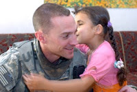 Noor Taha Najee gives 1st Lt. Michael Kendrick, platoon leader, 2nd Platoon, 1st Battalion, 30th Infantry Regiment, 2nd Brigade Combat Team, 3rd Infantry Division, a goodbye kiss near the end of a March 26 visit to her house in al Buaytha, Iraq. Noor, whose corneas are underdeveloped, has been blind since birth. The Soldiers of 1-30th Inf. Regt. are working with a nongovernmental organization in Los Angeles, the Eye Defects Research Foundation, to get Noor surgery that may provide her with sight. Photo by Sgt. Kevin Stabinsky.