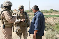 1st Lt. David B. Gilliland, a 24-year-old Civil Affairs team leader with Team 3, 2nd Battalion, 11th Marine Regiment, Regimental Combat Team 1, works with an interpreter to speak with an Iraqi contractor about an irrigation canal being built in Sophia area of Ramadi, Iraq, Oct. 8. Gilliland, originally from Florence, Ky., and the team of Civil Affairs Marines are working with the Government of Iraq to ensure the local farming community has access to several irrigation canals being built.