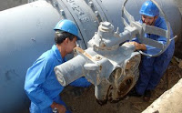 Two Iraqi technicians replace an old valve at one of the intake pipes at Sweetwater Canal Pump Station No. 2 located 90 kilometers from Basrah.