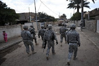 U.S. Soldiers support a joint patrol and search with Iraqi national policemen in Baghdad last month. The commander of Multi-National Force - Iraq says American troops could be out of Iraqi cities by June 30.