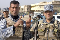 Two Iraqi Police officers display purple-stained fingers, signifying that they participated in Saturday's provincial elections.
