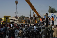 Children jump onto a flat-bed truck and celebrate as a crane removes several concrete barriers from a marketplace in Samarra, Iraq, March 23.