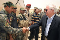 U.S. Defense Secretary Robert M. Gates talks with Iraqi security personnel July 28 during a site visit on Combined Operating Base Adder in Talil, Iraq.