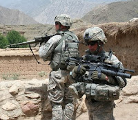 Sgt. Dustin Kaminiski and Staff Sgt. Johnny L. Bates stand guard in a small village in Kunar province Aug. 1.