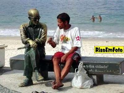Bêbado, no Rio de Janeiro, conversa seriamente com uma... ...estátua de Carlos Drummond de Andrade