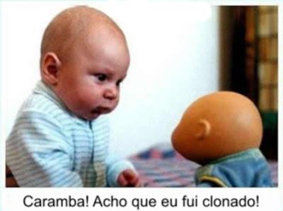 Descrição: Foto/Imagem engraçada onde um bebê olha intrigado para um boneco que se parece muito com ele.