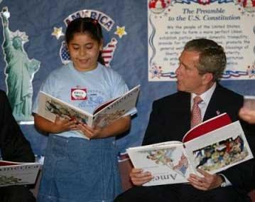 George Bush em pose estúpida, fingindo participar de uma aula, enquanto segura um livro de cabeça para baixo
