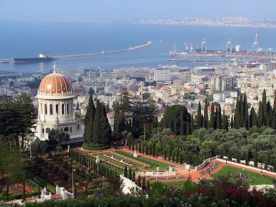 Imagem com vista panorâmica de Haifa com o Santuário Báb, o porto e a baía