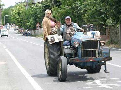 Homem e mulher em um trator sem uma das rodas