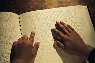 Fotografia de mãos a tactearem braille