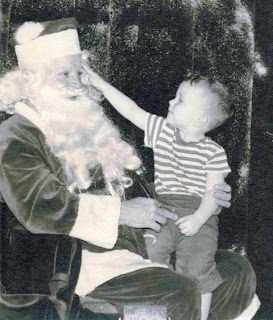 Thomas Kraemer sitting on the lap of Santa Claus pointing to his bushy eyebrows circa 1950s