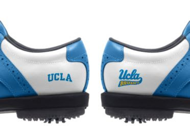 Blue UCLA golf shoes with two different logos reading UCLA in blue and a Ucla Brunins logo above a black rubber indoor cleat on the heel.