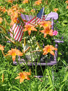 thrift shop chair as garden planter with flags