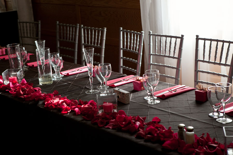 Black pintuck table cloth pink napkins rose petals with votive candles