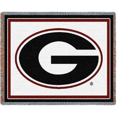 University of Georgia blanket that is white with a large black letter G in the middle of the throw.