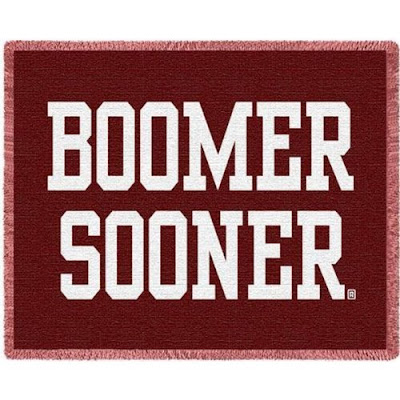 Boomer Sooner red blanket with cream colored writing.