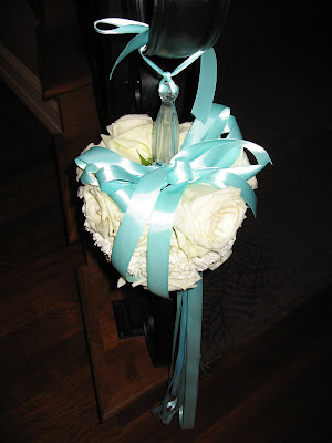 topiary at the end of the staircases roses accented with turquoise ribbon
