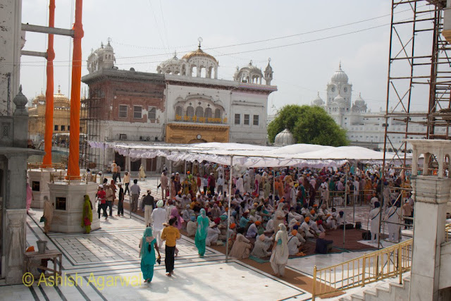 A view of the Nishaan Sahib, people at the langar and the Darshan Deori of the Golden Temple