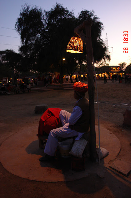 Photo of Villager dressed in traditional attire sitting under a lamp in Chokhi Daani