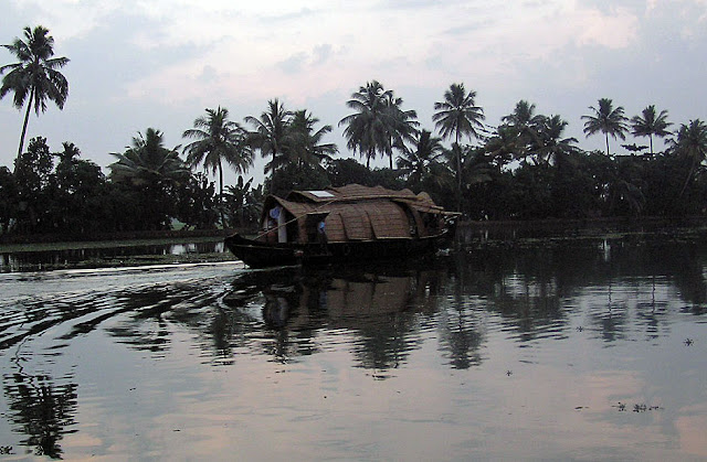View of a houseboat in Kerala, India making a turn, at sunset