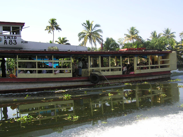 A boat carrying a number of people in the waterways near Alleppey, Kerala