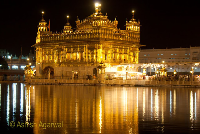Close up view of the Golden Temple,  the sarovar surrounding it, and the causway with devotees in Amritsar
