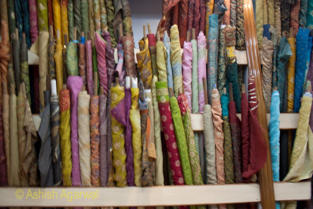 Bundles of pieces of cloth arranged at the side inside a shop in Amritsar