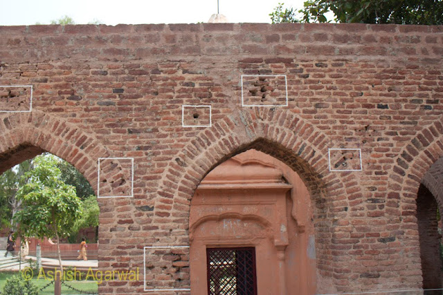 The remains of a small structure in the middle of the Jallianwala Bagh complex, with bullet marks